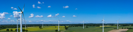 Panoramic aerial view and closeup of a wind turbine in a wind farm with rape field