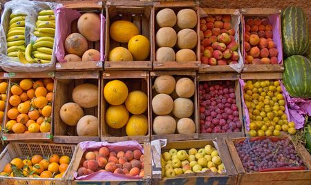 Fruit stand in a Moroccan market with melons, oranges, peaches, apricots, apples, etc.