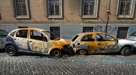 Two vandalised and burnt out cars on a street in rome Stock Photo