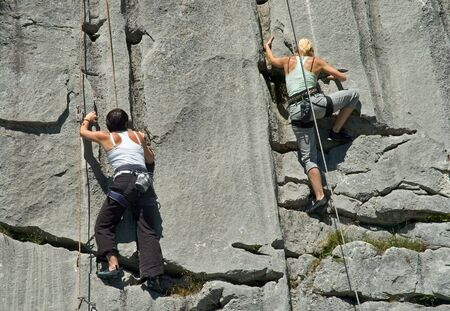repel: Two female rock climbers climbing limestone in Switzerland