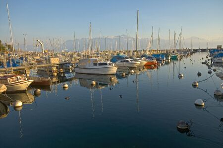 Boats and yachts in the docks at Vidy, Switzerland on Lake Geneva with the Alps in background