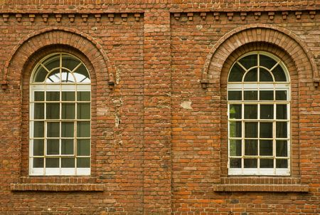 2 arched glass windows set in red brick wall Stock Photo