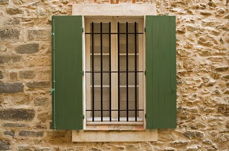 Old window with green shutters and old stone wall Stock Photo