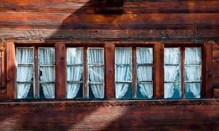 Row of four small windows in a traditional swiss wooden chalet
