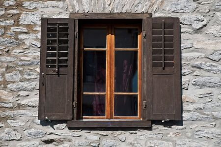 Old window with shutters on stone wall photo