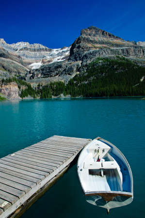 Small rowing boat at pier on a beautiful mountain lake