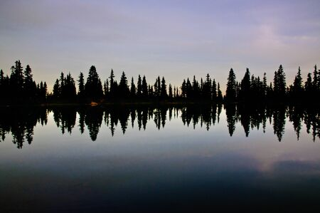 Lake reflection with silhouette of trees in the evening Stock Photo