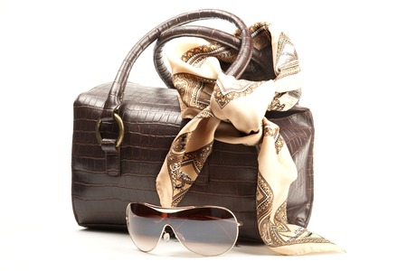 Brown bag, spectacles and scarf on the white background