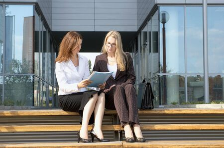 Two young businesswomen in front of an office building Stock Photo