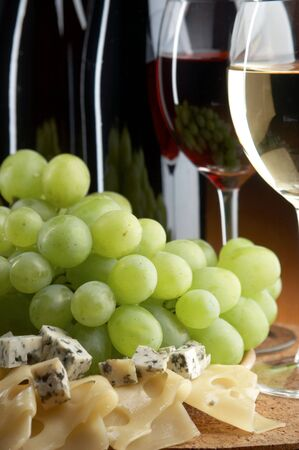 still life with grape, cheese, red and white wines on the black background photo