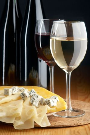 still life with cheeses, red and white wines on the black background Stock Photo