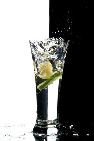 glass with water and lemon on the white and black background