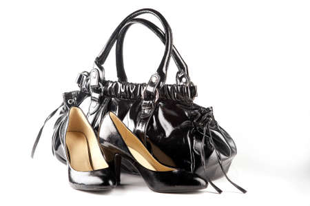 Black patent-leather shoes and bag on the white background