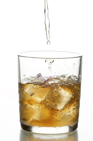 glass with whiskey and ice on the white background