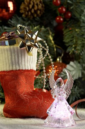 Angel and cristmas stocking with presents in front of fir tree Stock Photo - 2083287
