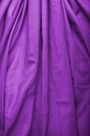 abstract background violet silk fabric with waves photo
