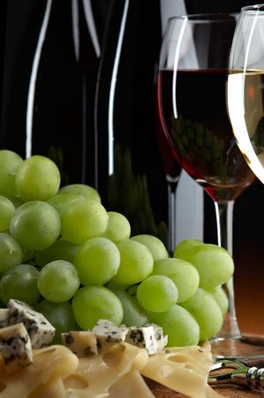 pervaded: still life with grape, cheese and wine on the black background Stock Photo