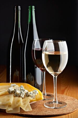 pervaded: still life with cheese, red and white wines on the black background