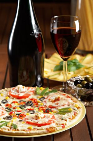 still life with red wine and pizza on the table photo
