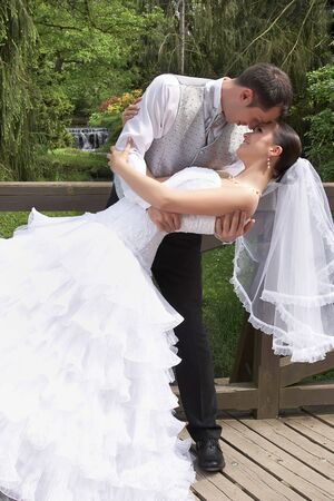 bridegroom and beautiful bride in white on the wedding in park photo