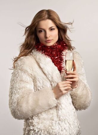Young beautiful woman in white fur coat with glass of �hampagne on the white background