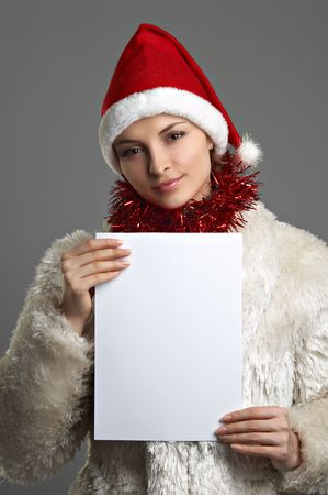 Young beautiful woman in white fur coat and red hat with sheet of paper on the grey background photo