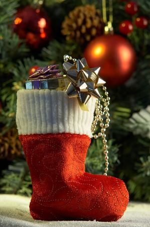 christmas stocking with presents in front of fir tree Stock Photo