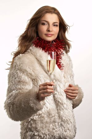 Young beautiful woman in white fur coat with glass of champagne on the white background photo