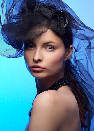 Young beautiful woman in black hat on the blue background photo