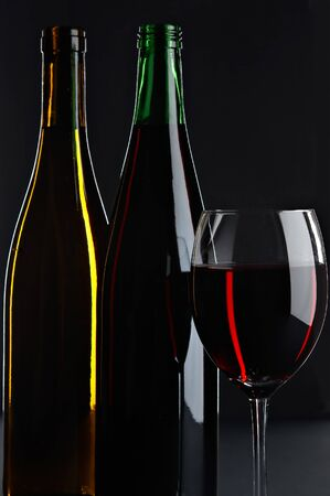 still life with red and white wines on the black background