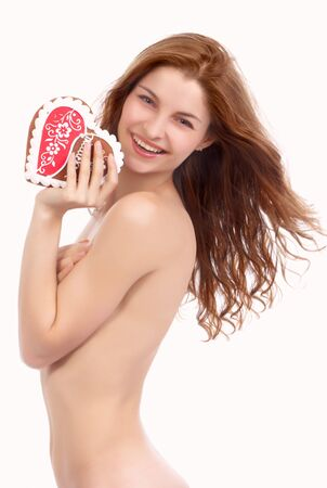Young beautiful woman with sweet red heart on the white background