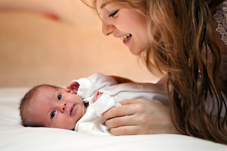 young mother smile with her newborn baby.  photo