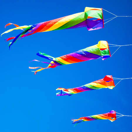 flying a kite: A formation of kites flying in a clear blue sky Stock Photo
