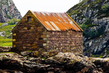 defiant: A stone hut standing defiant aginst the elements Stock Photo