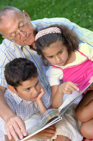 kids reading book: grandfather and kids reading book outdoors Stock Photo
