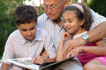 Happy grandfather and kids reading book outdoors photo