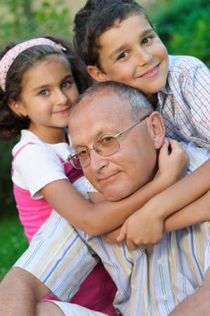 Happy grandfather and kids outdoors Stock Photo