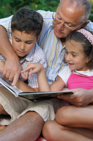 kids reading book: Grandfather and kids reading book outdoors