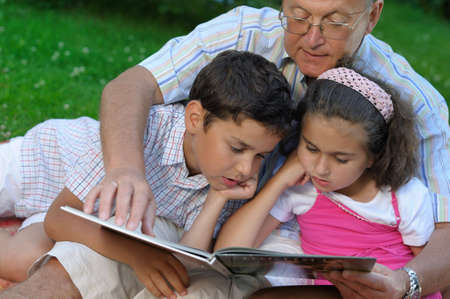 Grandfather and kids reading book Stock Photo
