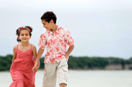 Happy kids walking on the beach photo