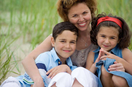 Happy mother and kids on the beach photo