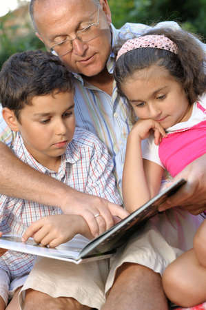 grandfather and kids reading book outdoors Stock Photo