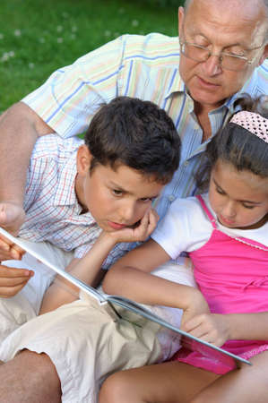 kids reading book: Grandfather and kids reading book Stock Photo