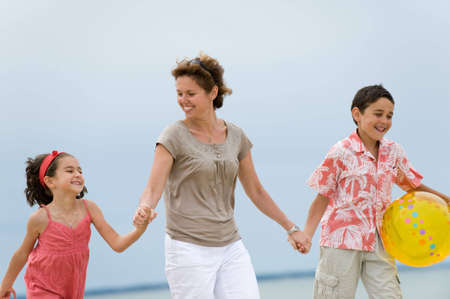 Happy mother and kids walking on the beach Stock Photo - 5062981