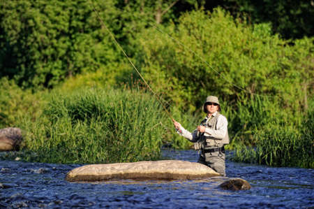 Fisherman on wild river Stock Photo