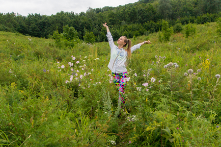 emotionality: Portrait of girl. Young girl enjoying nature among the wildflowers in a forest Stock Photo
