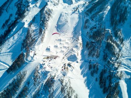 Paraglider flies over the mountains over the ski resort Reklamní fotografie