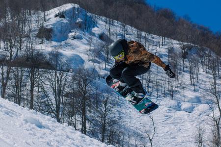 2017 04 Sochi, Russia, Festival NewStarCamp: snowboarder jumps from a high springboard Editorial