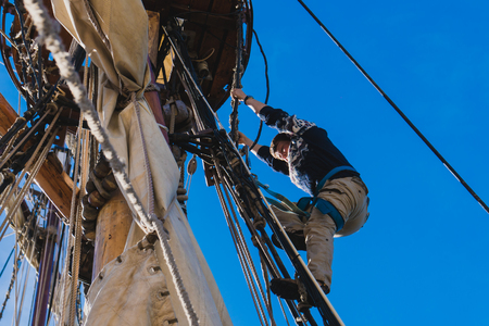 sailors work with sails at a height on a traditional sailboat in the sea