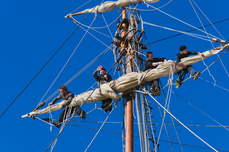 Sailors work with sails at a height on a traditional sailboat